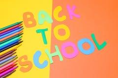 Indicatori multicolori ed iscrizione di nuovo alla scuola su un fondo giallo ed arancio Fotografie Stock