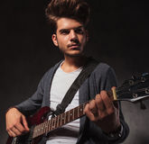 Indie artist playing guitar in studio background Stock Images