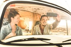 Indie couple ready for roadtrip on oldtimer mini van transport travel stock photography