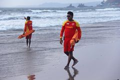 Indien, GOA, am 28. Januar 2018 Mannretter gehen entlang das Ufer in der roten Kleidung, Pfeife in der Pfeife, warnen von der Gef stockbilder