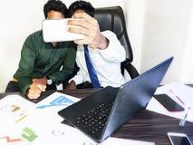 Indier för två ung vuxna människor som tar selfies på kontoret arkivbilder