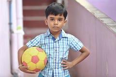 Indier Little Boy med fotboll royaltyfri bild