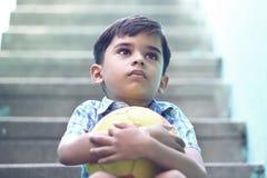 Indier Little Boy med fotboll royaltyfri foto