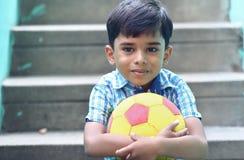 Indier Little Boy med fotboll arkivfoton