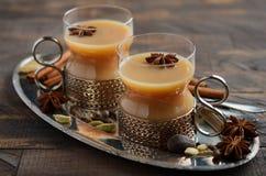 Indier Masala Chai Tea Kryddat te med mjölkar i koppar för en tappning på den lantliga trätabellen arkivbild