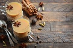 Indier Masala Chai Tea Kryddat te med mjölkar i koppar för en tappning på den lantliga trätabellen royaltyfri fotografi