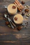 Indier Masala Chai Tea Kryddat te med mjölkar i koppar för en tappning på den lantliga trätabellen arkivfoton