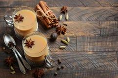 Indier Masala Chai Tea Kryddat te med mjölkar i koppar för en tappning på den lantliga trätabellen royaltyfria bilder