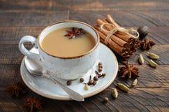 Indier Masala Chai Tea Kryddat te med mjölkar på den lantliga trätabellen arkivbild