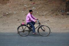 Indier på en cykel på en lantlig väg Arkivfoto
