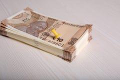 Indier 10 rupie valutaanmärkningar med det fäste all-stiftet arkivfoto