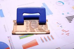 Indier 10 rupie valutaanmärkningar och stansamaskin på diagrampapperet arkivbild