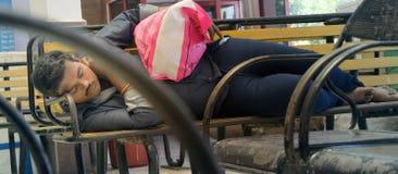Indier som vilar på stationsbänk Arkivfoton