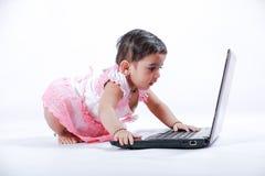 Indiern behandla som ett barn flickan med bärbara datorn royaltyfri foto