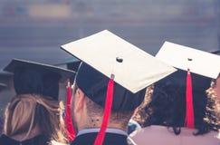 Indietro dei laureati durante l'inizio all'università, fine su al cappuccio laureato Graduation Immagini Stock