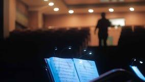 Indietro del conduttore e dei musicisti in sala da concerto e balaustro stock footage