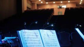 Indietro del conduttore e dei musicisti in sala da concerto e balaustro video d archivio