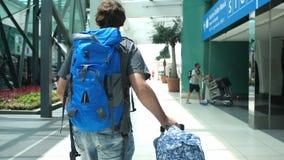 Indietro del punto di vista del giovane con lo zaino che tira valigia in terminale di aeroporto moderno Camminata bella di viaggi fotografia stock libera da diritti