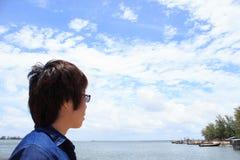 Indietro della camicia dei jeans di usura del giovane che guarda e che pensa sopra il villaggio del pescatore Immagine Stock
