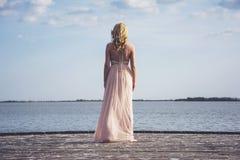 Indietro della donna bionda nella posa del vestito da sera Immagini Stock