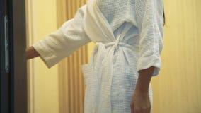 Indietro della giovane donna avvolta in abito bianco entra nella sauna nel salone della stazione termale archivi video