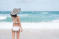 Indietro della giovane donna in bikini che sta sulla spiaggia, giovane bella donna sexy in costume da bagno del bikini, isola tro immagini stock