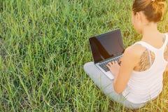 Indietro della giovane donna che per mezzo del computer portatile ai prati Fotografia Stock Libera da Diritti