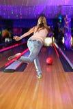 Indietro della ragazza che fa tiro della sfera nel randello di bowling Immagine Stock