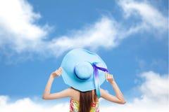 Indietro della ragazza che tiene un cappello con cielo blu Fotografia Stock