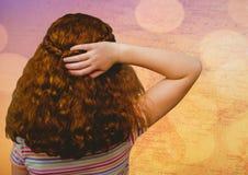 Indietro della ragazza con la mano su capelli contro la mappa con bokeh Fotografia Stock