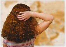 Indietro della ragazza con la mano su capelli contro la mappa marrone confusa Immagini Stock Libere da Diritti