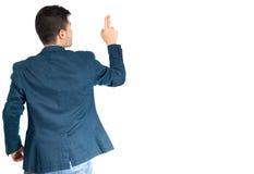 Indietro di un uomo di affari che tocca qualcosa al fondo bianco Fotografia Stock