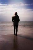 Indietro di una giovane donna che sta sulla spiaggia Immagini Stock