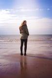 Indietro di una giovane donna che sta sulla spiaggia Fotografie Stock