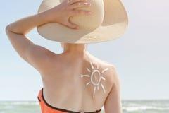 Indietro di una ragazza con un sole crema dipinto immagine stock