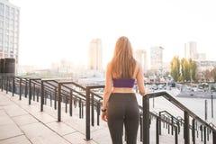 Indietro di una ragazza di sport in ghette e cime contro lo sfondo di un paesaggio della città al tramonto immagini stock libere da diritti