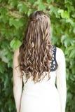 Indietro vista di capelli marroni lungamente arricciati con la treccia della cascata Fotografia Stock