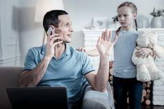 Indifferent dad speaking on the mobile phone Stock Photo