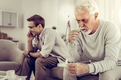 Old man taking pills while son indifferently having a phone call. royalty free stock photos