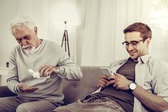 Indifferent grandchild looking at phone meanwhile his granddad taking pills. Indifferent grandchild. Indifferent happy grandchild in glasses cheerfully looking royalty free stock images