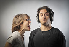Indifferent husband. Angry women screaming against her husband pretending not to listen to her Stock Photos
