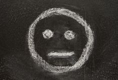 Indifferent. Icon. Expressionless emoticon face. Neutral smiley mood, sketched with white chalk on the blackboard Stock Images