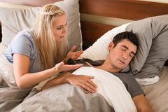 Indifferent man sleeping in bed next to his partner. Indifferent or exhausted young men sleeping in bed next to his frustrated partner Stock Image