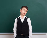 Indifferent school boy portrait near green blank chalkboard background, dressed in classic suit, one pupil, education concept Stock Image