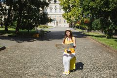 Indifferent traveler tourist woman in yellow clothes, hat sitting on suitcase looking on city map search route outdoor. Girl traveling abroad to travel on royalty free stock image
