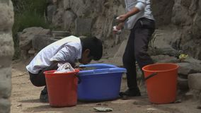 Indigenous children washing shoes in Bolivian village stock video footage