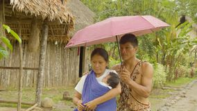 Indigenous family in the rain. Indigenous people taking their baby to the doctor in the rain in Ecuador stock video footage