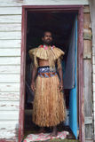 Indigenous Fijian man dressed in traditional Fijian costume. Stand in front of his home doorway at the village. Real people, copy space Royalty Free Stock Image