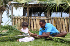 Indigenous Fijian man teach young tourist girl how to create a b Royalty Free Stock Photo