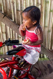 Indigenous girl sitting on a bicyclic and eating bread with jam Royalty Free Stock Image
